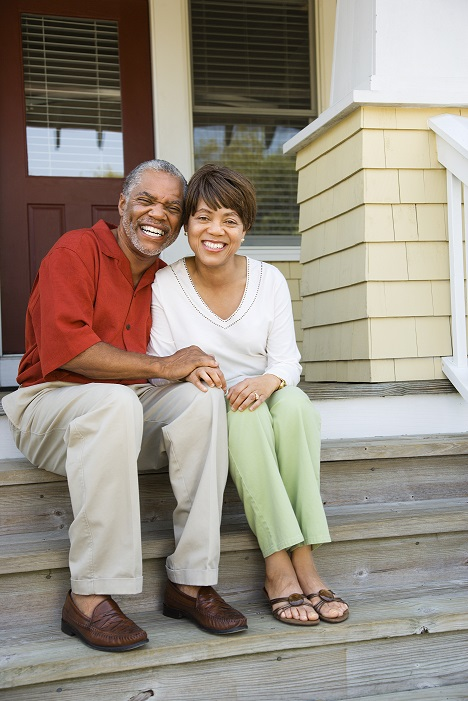 Image of an older couple sitting on the steps in front of a house