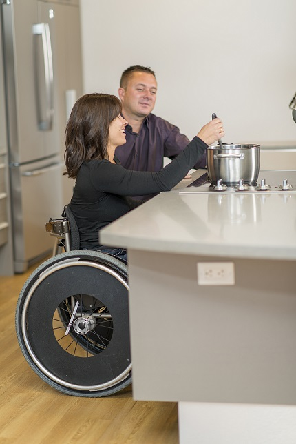 Image of a woman in a wheel chair at a stove cooking